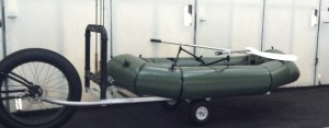 Bicycle trailer , flat bed with the optional fly rod rack and show with a float boat equipped with oars and rowing frame.